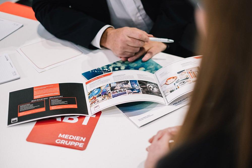 hochwertige und veredelt gedruckte Flyer liegen auf einem Tisch und werden präsentiert