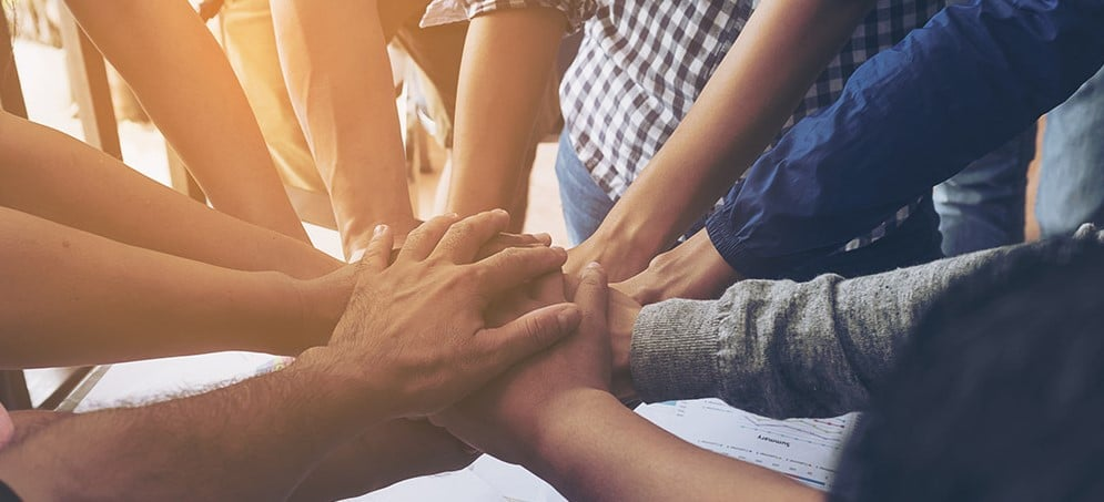 Teamhände die gemeinsam die Hände in die Mitte legen und sich festhalten