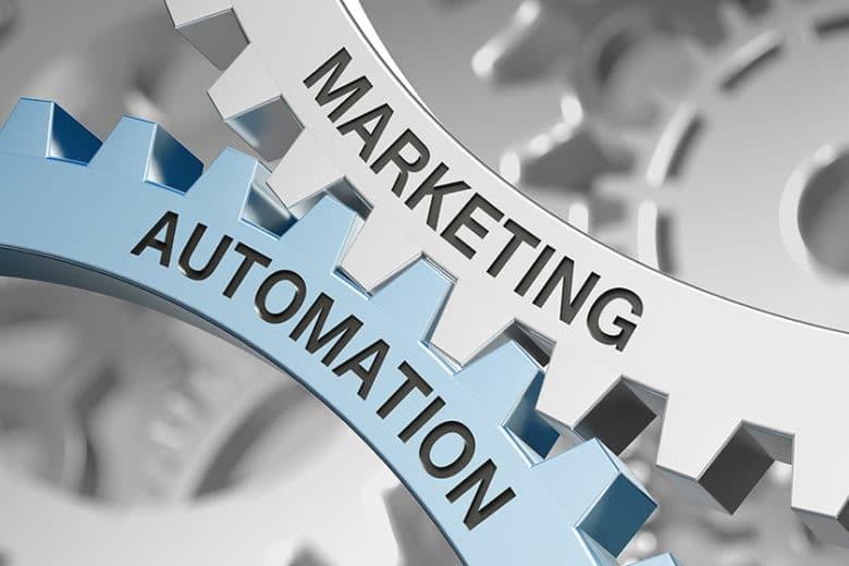 Es sind zwei in sich ineinandergreifende Zahnräder zu sehen mit der Aufschrift Marketing und Automatisierung