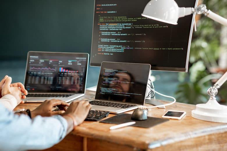 Anwendungsentwicklung und Webentwicklung durch eine Agentur anhand von mehreren Monitoren mit Codezeilen