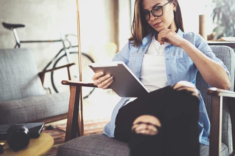 Eine Frau sitzt in einem Sessel und schaut auf ein Tablet. Der Inhalt wurde automatisiert erstellt.