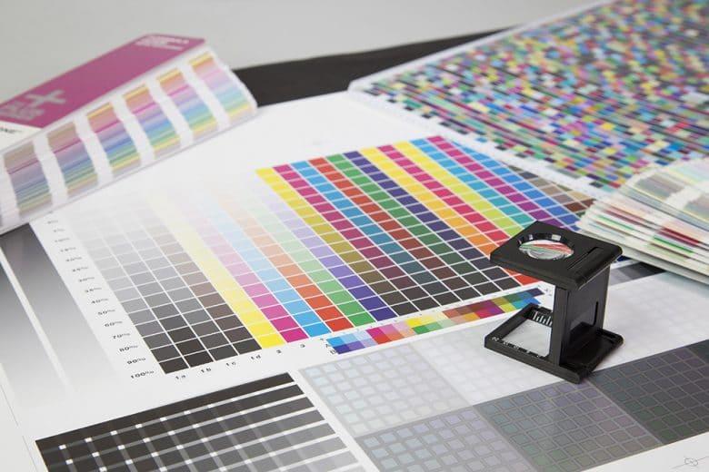 Mehrere gedruckte Bogen mit Farbfeldern auf denen eine Lupe steht