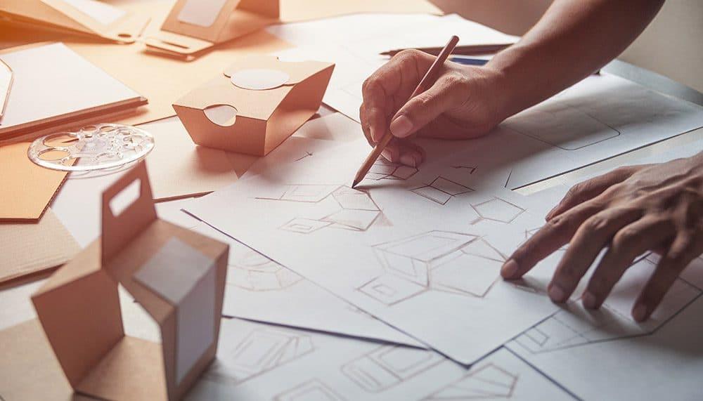 Man sieht eine Hand, die unterschiedliche Zeichnungen und Skizzen auf Papier malt