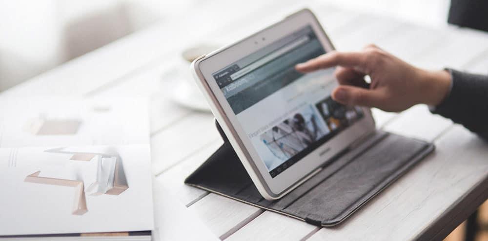 Jemand berührt ein Tablet über das eine digitale Ebene schwebt mit unterschiedlichen Grafiken zu digitalem und print Marketing