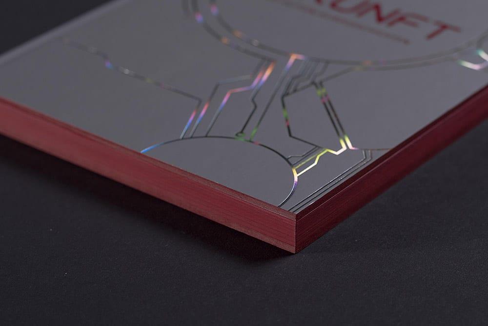 Es ist ein Ausschnitt eines hochwertig gedruckten und mit Folie und Farbschnitt veredelten Buches zu sehen