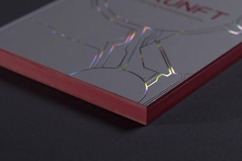 Ein Ausschnitt von einem sehr hochwertig gedruckten und veredelten Buch mit rotem Farbschnitt am Rand und Folienprägung