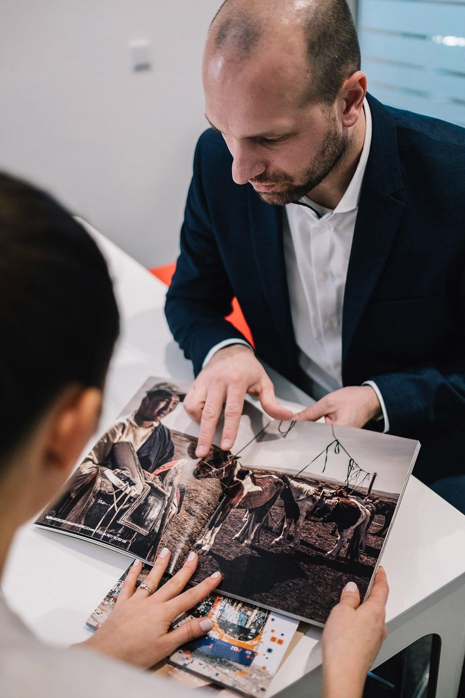 Ein Mann mit Bart präsentiert ein hochwertig gedrucktes Magazin einer Frau