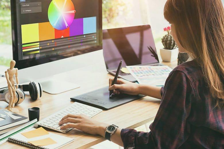 Eine Frau sitzt vor einem Monitor und erstellt Grafiken und Designs