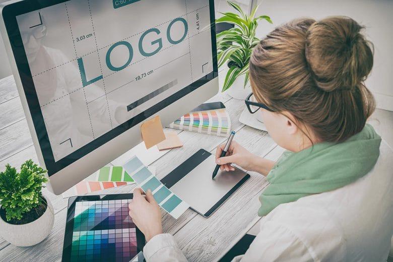 Eine Frau sitzt vor einem Monitor und gestaltet ein Logo