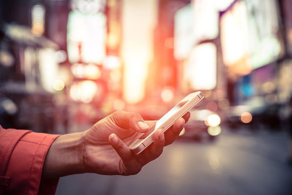 Jemand hat ein Handy in der Hand, im Hintergrund ist unscharf eine Stadt zu erkennen