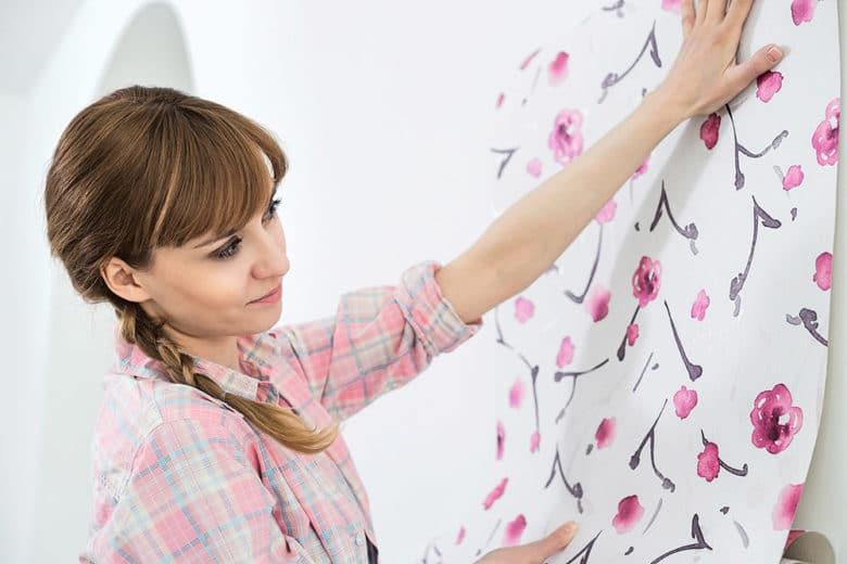 Eine junge Frau tapeziert eine Wand mit einer bunten Tapete
