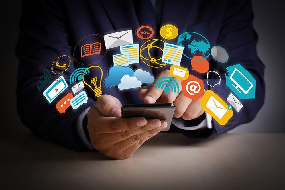 Ein Mann tippt auf ein Smartphone, verscheidene Icons sind über dem Smartphone zu sehen