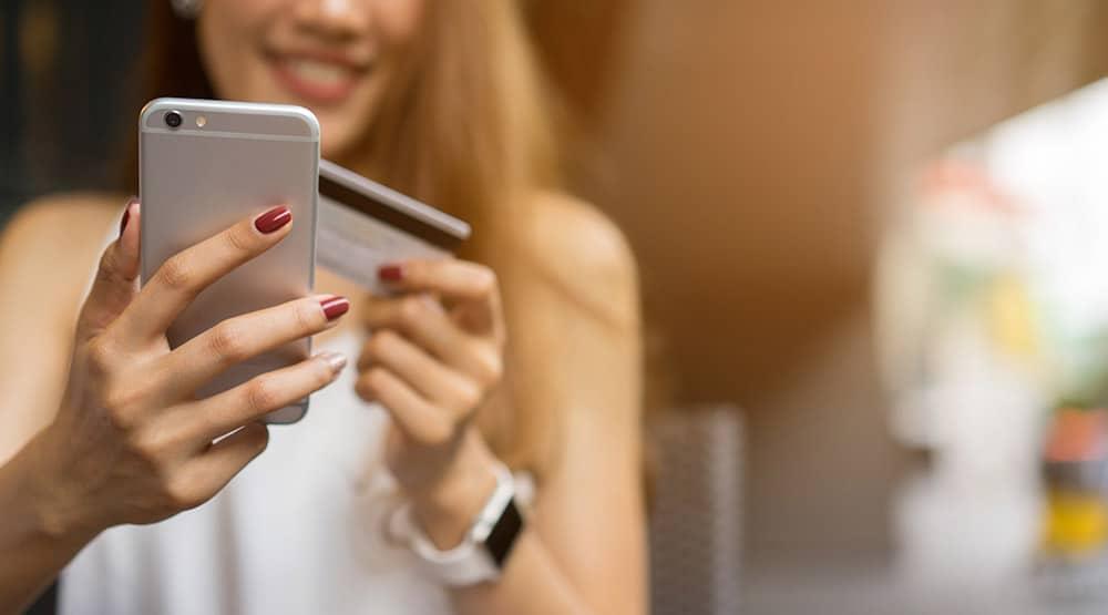 Eine Frau ist von vorne zu sehen, die ein silbernes Handy in der Hand hat und eine Kreditkarte in der anderen