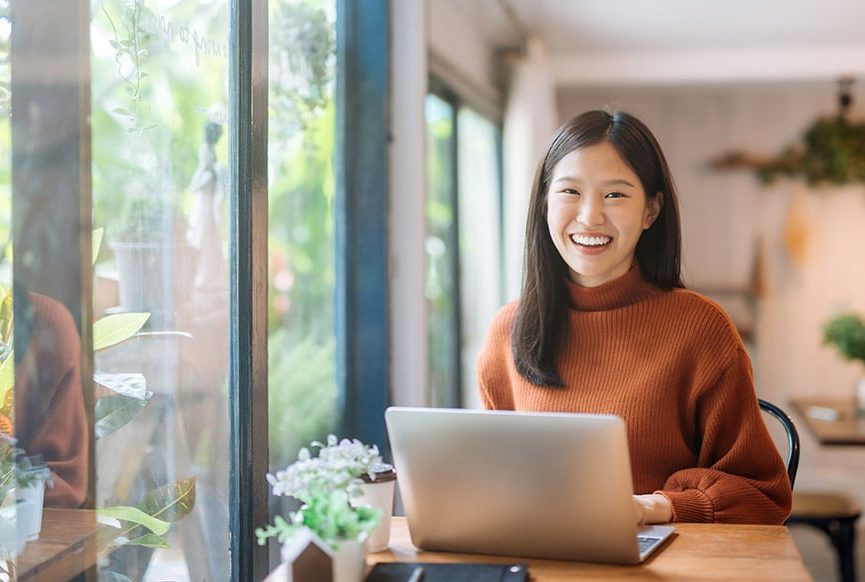 Eine Frau die ein Laptop auf ihrem Schoß hat und freundlich lächelt