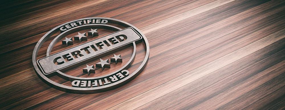 Auf einem holzähnlichen Untergrund ist ein Logo mit dem Wort Certified.