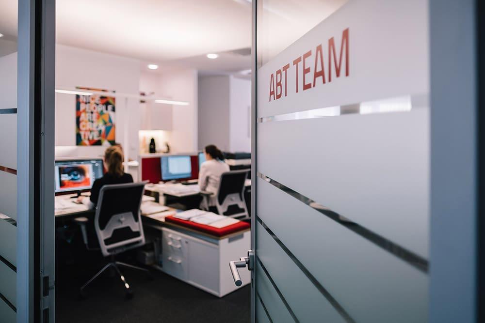 Geöffnete Tür zu ABT Büroräumlichkeiten mit der Aufschrift ABT TEAM
