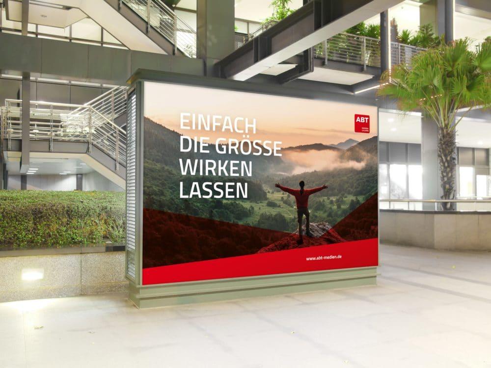 gedrucktes Displays, beziehungsweise Großflächenplakat an einer Straße mit Werbung