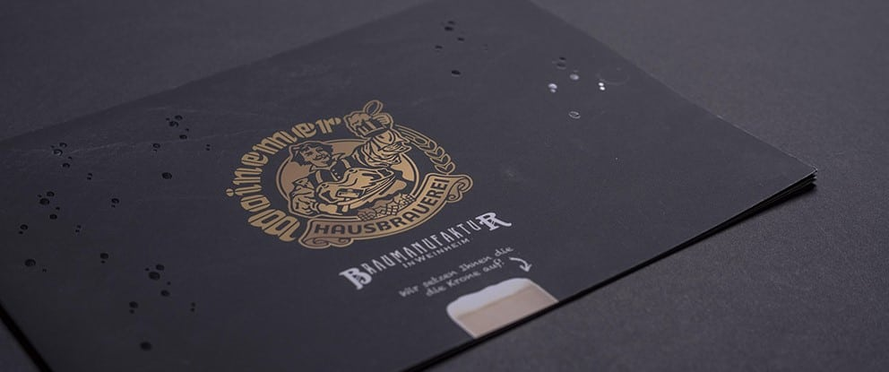 Druckereibroschüre veredelt mit Goldlack liegt auf grauem Untergrund