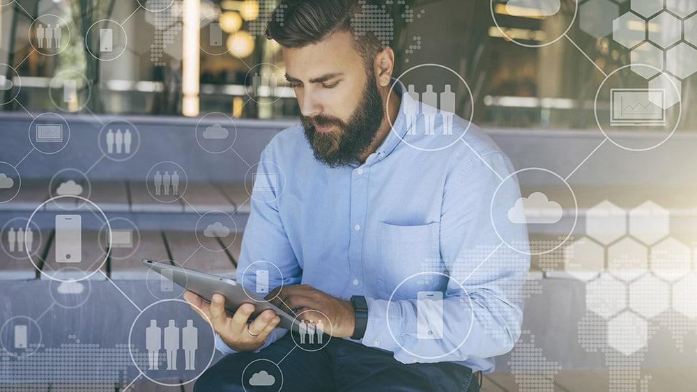 Ein Mann mit Bart schaut auf sein Tablet und davor sind transparente Grafiken und Icons zu Personen, Tablets, Handys zu sehen