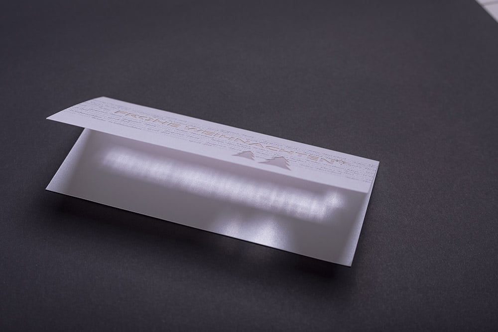 Eine aufgeklappt, querformatige Weihnachtskarte die hochwertig gedruckt und mit einer Laserstanzung im Titel veredelt ist