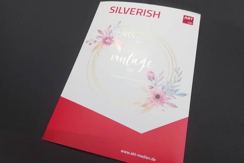 hochwertig gedruckter Flyer mit Grafiken, die durch unterdrucken von Gold und Silber iriodirisierend wirken