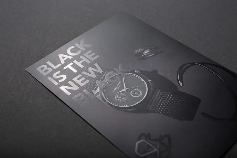 """Ein DIN A4 Flyer, der vollflächig schwarz bedruckt ist und mit einer partiellen Lackierung den Satz """"black is the new black"""" veredelt hat"""