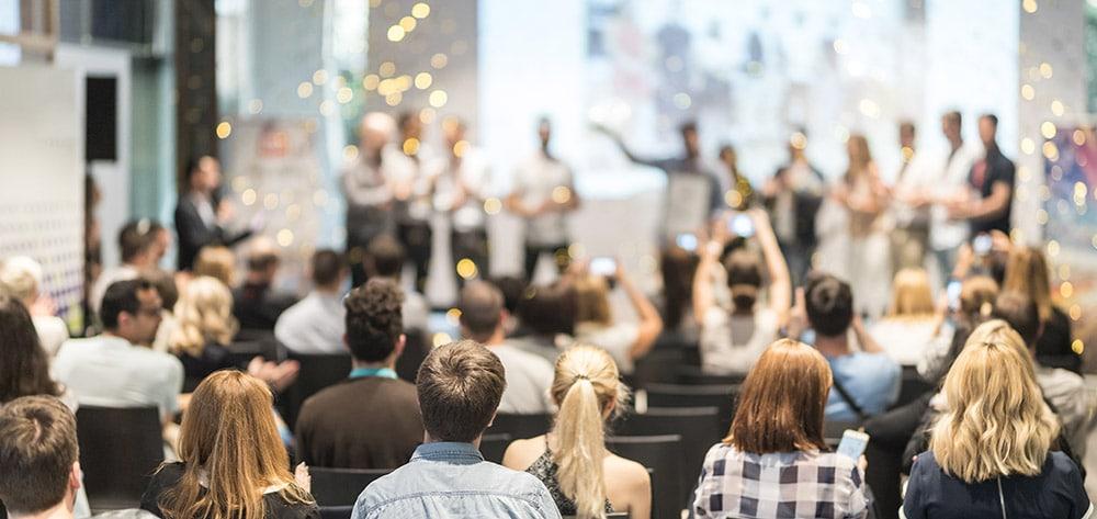 Es ist ein jubelndes Publikum vor einer Bühne bei einer Preisverleihung zu sehen.