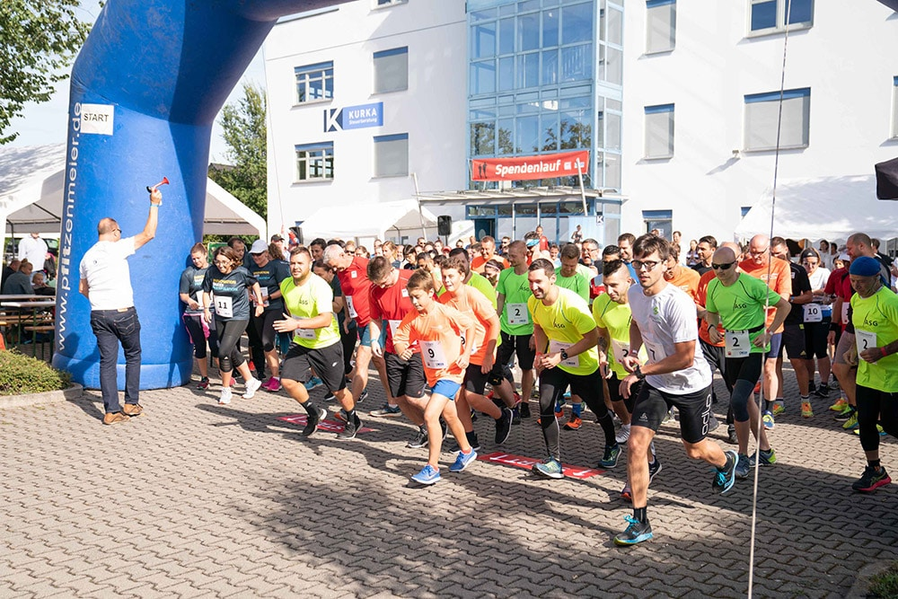 Es ist der Start des ABT Spendenlaufs 2019 zu sehen. Nach dem Startschuss rennt die Menschenmasse los.
