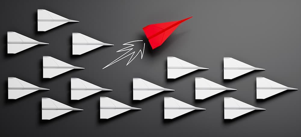 Es sind mehrere Flieger zu sehen, die alle identisch sind bis auf einen und hintereinander fliegen. Der anders aussehende Flieger wechselt seine Richtung und fliegt den anderen Fliegern nicht mehr hinterher