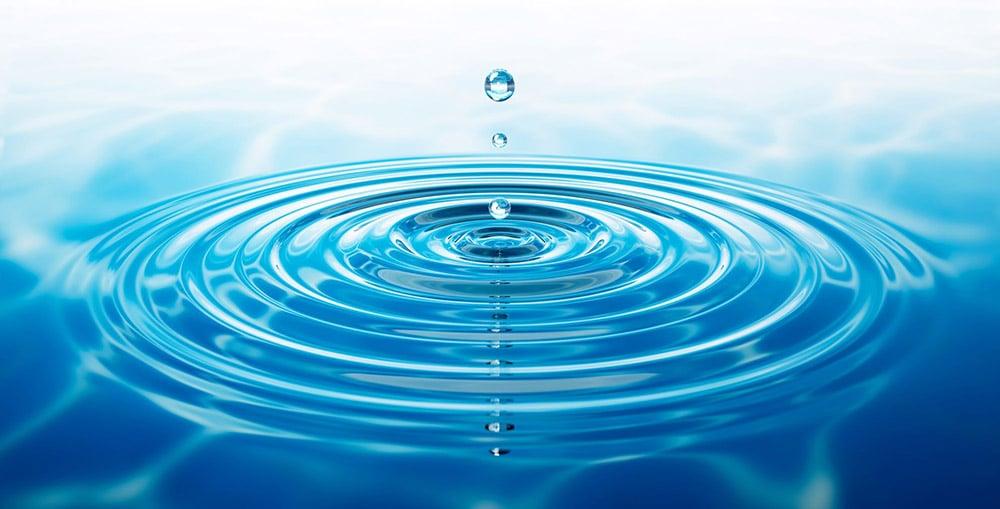 Ein Wassertropfen trifft auf die Wasseroberfläche ein und zieht seine Kreise.