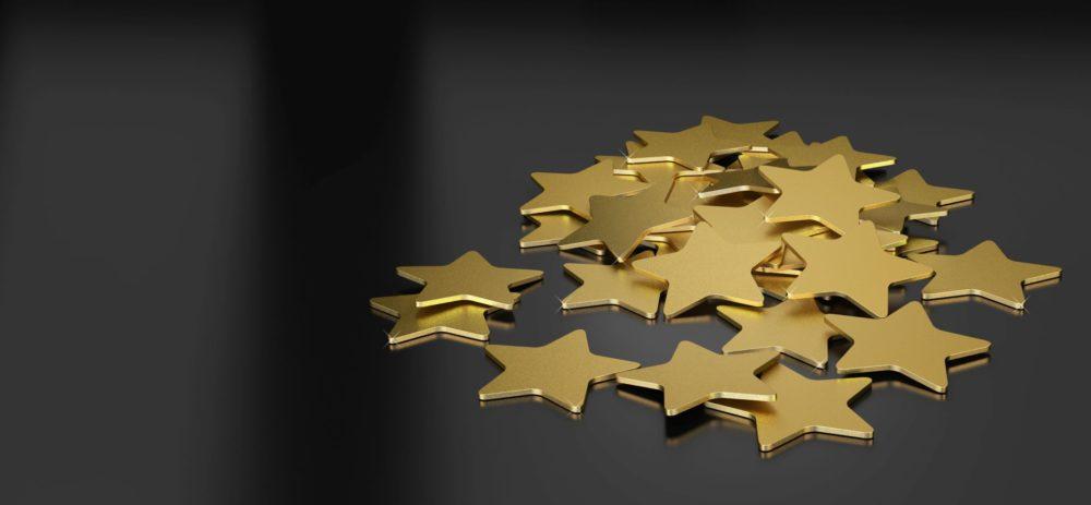 Auf einem schwarzen, hochwertigen Untergrund liegen goldene kleine Sterne